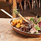 Lammhaxl nach Bauernart  mit Bohnenbündel und Bratkartoffeln